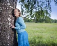 La mujer joven hermosa en un vestido azul en el campo en un abedul Imágenes de archivo libres de regalías
