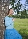 La mujer joven hermosa en un vestido azul en el campo en un abedul Imagenes de archivo