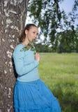 La mujer joven hermosa en un vestido azul en el campo en un abedul Imagen de archivo libre de regalías