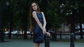 La mujer joven hermosa en un vestido azul se está colocando solamente en la ciudad almacen de video