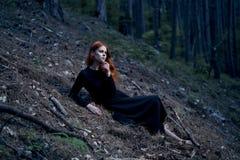 La mujer joven hermosa en un vestido negro largo miente en un bosque oscuro Foto de archivo libre de regalías