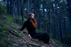 La mujer joven hermosa en un vestido negro largo se está sentando en un bosque oscuro Imágenes de archivo libres de regalías