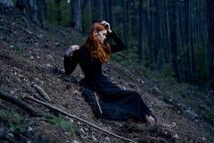 La mujer joven hermosa en un vestido negro se está sentando en un bosque oscuro Foto de archivo