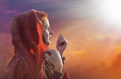 La mujer joven hermosa en una bufanda ruega a dios Fotos de archivo