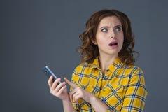 La mujer joven hermosa en una camisa amarilla expresa emociones con Foto de archivo libre de regalías