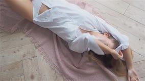 La mujer joven hermosa en una camisa blanca está mintiendo en el piso