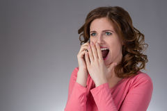 La mujer joven hermosa en una camisa rosada expresa emociones con s Foto de archivo