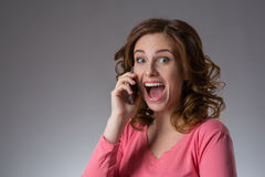 La mujer joven hermosa en una camisa rosada expresa emociones con s Fotos de archivo libres de regalías