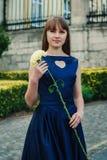 La mujer joven hermosa en vestido azul sostiene la flor Imagenes de archivo