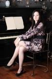 La mujer joven hermosa en vestido se sienta en el piano viejo negro Imagenes de archivo
