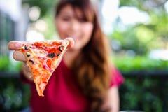 La mujer joven hermosa encantadora es que sostiene y que muestra la pizza deliciosa o deliciosa It's un poco de comida italiana foto de archivo libre de regalías