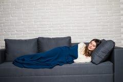 La mujer joven hermosa es durmiente y que ve sueños dulces en el sofá en casa Fotografía de archivo
