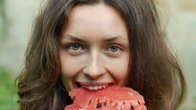 La mujer joven hermosa está comiendo la sandía con placer y mirada en la cámara almacen de metraje de vídeo