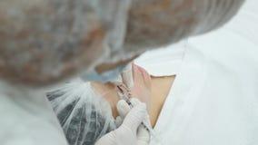 La mujer joven hermosa está consiguiendo la inyección del botox en su mejilla metrajes