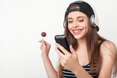 La mujer joven hermosa está gozando del caramelo y Imagenes de archivo