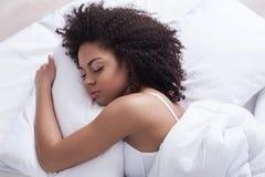 La mujer joven hermosa está medio dormida en dormitorio Imagenes de archivo