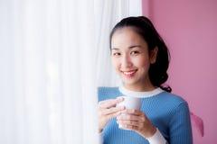 La mujer joven hermosa está mirando hacia fuera la ventana y está sosteniendo una taza Imagen de archivo libre de regalías