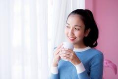 La mujer joven hermosa está mirando hacia fuera la ventana y está sosteniendo una taza de café Fotos de archivo