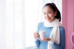 La mujer joven hermosa está mirando hacia fuera la ventana y está sosteniendo una taza de café Foto de archivo libre de regalías