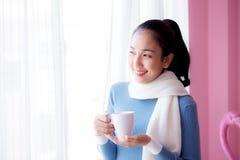 La mujer joven hermosa está mirando hacia fuera la ventana y está sosteniendo una taza de café Imágenes de archivo libres de regalías