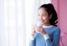 La mujer joven hermosa está mirando hacia fuera la ventana y está sosteniendo una taza de café por mañana Imágenes de archivo libres de regalías