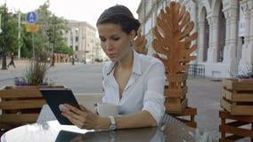 La mujer joven hermosa está utilizando una tableta digital en un café metrajes