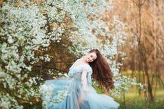 La mujer joven hermosa feliz con el pelo sano negro largo disfruta de las flores frescas y de la luz del sol en parque del flor e Foto de archivo libre de regalías