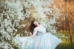 La mujer joven hermosa feliz con el pelo sano negro largo disfruta de las flores frescas y de la luz del sol en parque del flor e Imágenes de archivo libres de regalías