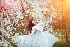 La mujer joven hermosa feliz con el pelo sano negro largo disfruta de las flores frescas y de la luz del sol en parque del flor e Fotografía de archivo