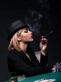 La mujer joven hermosa fuma un cigarro durante un juego de póker Fotografía de archivo libre de regalías
