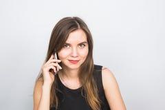 La mujer joven hermosa habla hablar por el teléfono móvil, en un fondo blanco Foto de archivo