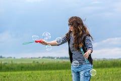 La mujer joven hermosa hace burbujas que soplan Fotos de archivo