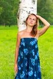 La mujer joven hermosa hace una pausa el árbol de abedul Imagenes de archivo