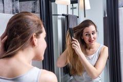 La mujer joven hermosa infeliz que cepilla su largo seca el pelo enredado Foto de archivo libre de regalías