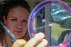 La mujer joven hermosa interesante mira se en el espejo y los palillos con las piedras que brillan del cuchillo del cortador en l fotografía de archivo libre de regalías