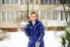 La mujer joven hermosa juega bolas de nieve Imágenes de archivo libres de regalías