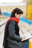 La mujer joven hermosa lee el libro imagen de archivo