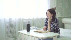 La mujer joven hermosa lee un libro, utiliza a un ayudante de la voz, tiene una pregunta