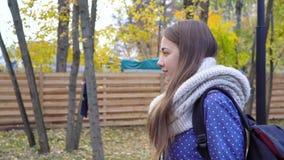 La mujer joven hermosa lleva la bufanda hecha punto y caminar en parque del otoño Movimiento video almacen de video