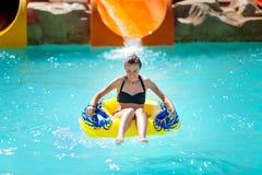 La mujer joven hermosa lleva a cabo las diapositivas en parque del agua Foto de archivo
