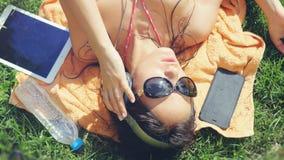 La mujer joven hermosa lleva las gafas de sol que mienten en la hierba, escuchando la música y canción del canto Imágenes de archivo libres de regalías