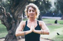 La mujer joven hermosa medita en el asana Padmasana de la yoga - la actitud de Lotus en la cubierta de madera en el parque del ot foto de archivo