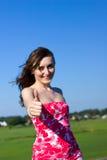 La mujer joven hermosa muestra el pulgar para arriba Imagen de archivo libre de regalías