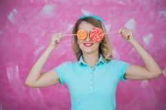 La mujer joven hermosa oculta ojos con las piruletas dulces sobre rosa Foto de archivo libre de regalías