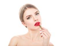 La mujer joven hermosa pinta los labios con el lápiz labial Maquillaje perfecto Imágenes de archivo libres de regalías