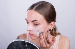 La mujer joven hermosa pone friega la crema en su cara Imagen de archivo