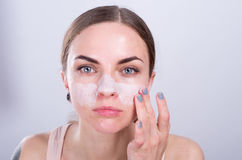 La mujer joven hermosa pone friega la crema en su cara Fotos de archivo