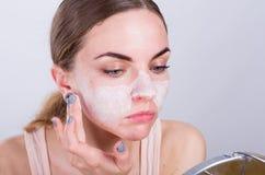 La mujer joven hermosa pone friega la crema en su cara Imagenes de archivo