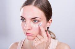 La mujer joven hermosa pone la crema en su cara Fotos de archivo