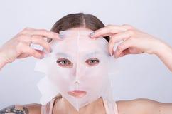 La mujer joven hermosa pone la máscara antienvejecedora en su cara Foto de archivo libre de regalías